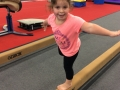 young girl on gym beam